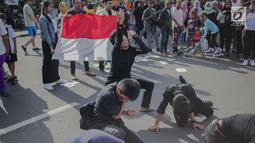 Massa yang tergabung dalam Presidium Mahasiswa Bela Rakyat (PMBR) menggelar aksi teatrikal di kawasan Bundaran HI, Jakarta, Minggu (14/4). Aksi tersebut mengajak agar masyarakat siapa pun pilihannya kita tetap Indonesia. (Liputan6.com/Faizal Fanani)