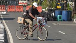 Seorang pedagang melintas dekat jalan yang ditutup menuju Gedung Mahkamah Konstitusi (MK) di Jakarta, Kamis (27/6/2019). Rekayasa lalu lintas sudah disiapkan di sekitar gedung MK selama pelaksanaan sidang pembacaan putusan hasil sengketa pilpres 2019. (merdeka.com/Imam Buhori)