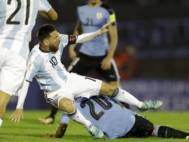 Pemain Argentina, Lionel Messi terjatuh saat berebut bola dengan pemain Uruguay, Alvaro Gonzalez pada laga kualifikasi Piala Dunia 2018 di Montevideo, Uruguay, (31/8/2017). Argentina bermain imbang 0-0. (AP/Natacha Pisarenko)