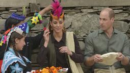 Duchess of Cambridge, Kate Middleton didampingi suaminya Pangeran William tersenyum saat seorang wanita dari Suku Kalash memakaikan topi tradisional yang mirip mahkota selama kunjungan ke pemukiman Chitral di Pakistan (16/10/2019). (AFP Photo/Farooq Naeem)