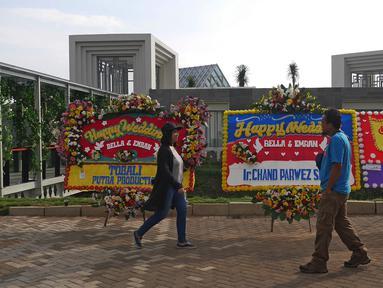 Pejalan kaki melintasi karangan bunga ucapan selamat untuk Laudya Cynthia Bella dan Engku Emran di lokasi resepsi pernikahan kawasan Dago, Bandung, Minggu (8/10). Bella dan Emran resmi menikah pada 8 September 2017. (Liputan6.com/Herman Zakharia)