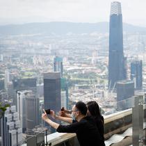 Turis dengan mengenakan masker mengambil gambar dari dek obseravsi di Menara Kuala Lumpur di Kuala Lumpur, Rabu (1/7/2020). Malaysia memasuki pelonggaran Perintah Kontrol Gerakan (MCO) setelah tiga bulan pembatasan karena virus corona Covid-19. (AP Photo/Vincent Thian)
