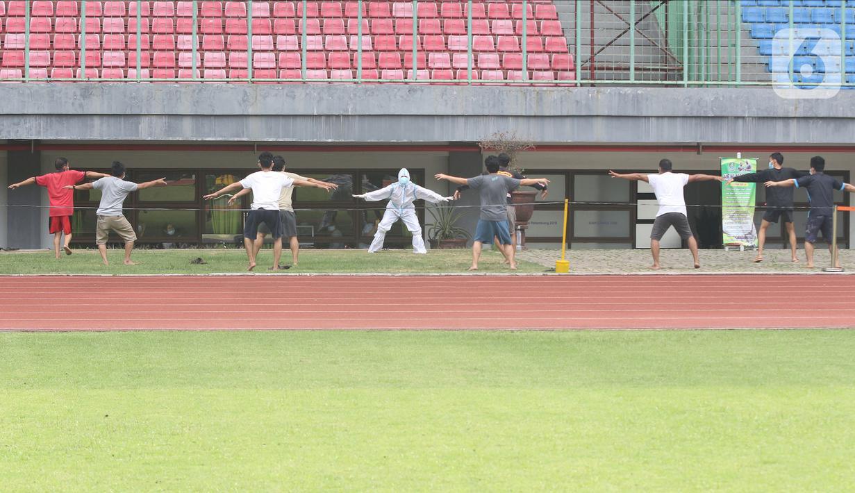Sejumlah pasien berstatus orang tanpa gejala (OTG) senam bersama tim medis di Stadion Patriot Chandrabaga, Bekasi, Jawa Barat, Minggu (27/9/2020). Dari 28 pasien OTG, beberapa di antaranya mengikuti senam di arena stadion karena masih menunggi hasil pemeriksaan. (Liputan6.com/Herman Zakharia)