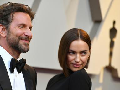 Aktor Bradley Cooper dan model asal Rusia, Irina Shayk  menghadiri perhelatan Oscar 2019 di Dolby Theatre, Los Angeles, Minggu (24/2). Di tengah isu kedekatannya dengan Lady Gaga, Cooper justru tampil mesra dengan Irina Shayk. (Jordan Strauss/Invision/AP)