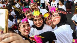 """Sejumlah peserta berfoto sebelum mengikuti flashmob 1745 penari di kawasan Senayan, Jakarta, Minggu (21/8). Kegiatan bertajuk """"Aku Indonesia-Bagimu Negeri Kami Menari"""" itu merupakan bagian dari perayaan HUT RI ke 71. (Liputan6.com/Fery Pradolo)"""