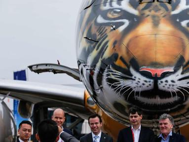 Pengunjung berpose di depan pesawat Embraer E190-E2 yang dipamerkan pada ajang Singapore Airshow 2018 di Changi, Singapura, (7/2). Embraer memamerkan secara perdana pesawat E190-E2 dengan design harimau dibagian kepala. (AP Photo / Yong Teck Lim)
