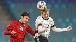 Gelandang Jerman, Julian Brandt, berebut bola dengan bek Republik Ceko, Ales Mateju, pada laga uji coba di RB Arena, Kamis (12/11/2020) dini hari WIB. Jerman menang 1-0 atas Republik Ceko. (AFP/Odd Andersen)