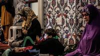 Seorang anak laki-laki bermain telepon ketika ibunya dan para wanita Muslim lainnya berdoa pada malam pertama salat tarawih di Masjid Nizamiye di Midrand, Johannesburg, Afrika Selatan (16/5). (AFP Photo/Gulshan Khan)