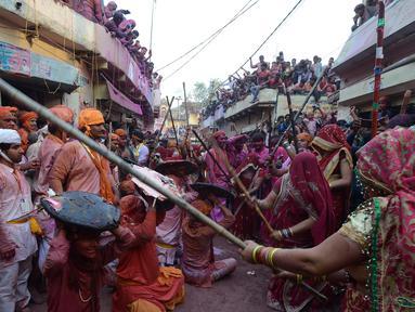 Sejumlah wanita memukul pria dengan tongkat (lathi) selama perayaan Lathmar Holi di Barsana di Mathura, India, (24/2). Lathmar Holi adalah perayaan lokal festival Hindu Holi, biasanya beberapa hari sebelum festival Holi. (AFP Photo/Dominique Faget)