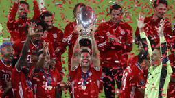 Pemain Bayern Munchen, Robert Lewandowski, mengangkat trofi gelar juara Piala Super Eropa 2020 usai mengalahkan Sevilla di Puskas Arena, Budapest, Jumat (25/9/2020) dini hari WIB. Bayern Munchen menang 2-1 atas Sevilla. (AFP/Laszlo Balogh/pool)