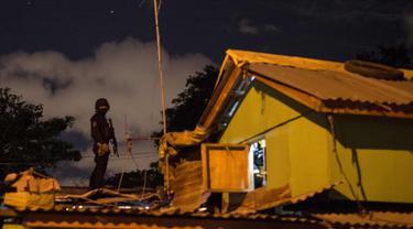 Seorang polisi terus berjaga dari atap selama penggerebekan bandar narkoba di Desa Maharlika, Taguig, selatan Manila (28/2). Penggerebekan dilakukan untuk menangkap lima pengedar narkoba, namun hanya dua yang ditangkap. (AFP Photo/Noel Celis)