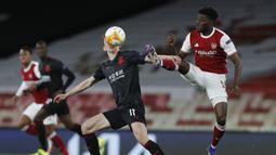 Gelandang Arsenal, Thomas Partey (kanan) berebut bola dengan gelandang Slavia Praha, Lukas Provod dalam laga leg pertama perempatfinal Liga Europa 2020/2021 di Emirates Stadium, London, Kamis (8/4/2021). Arsenal bermain imbang 1-1 dengan Slavia Praha. (AP/Alastair Grant)