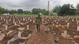 Petugas berjalan di antara makam jenazah dengan protokol COVID-19 di TPU Bambu Apus, Jakarta Timur, Selasa(16/2/2021). Pemangkasan petak makam di TPU Bambu Apus tersebut dilakukan agar bisa menampung lebih banyak jenazah, mengingat lahan pemakaman terbatas. (Liputan6.com/Herman Zakharia)