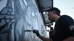 Seniman grafiti membuat mural harimau kumbang di Bangkok, Thailand (16/3). Aksi ini sebagai protes perburuan liar ilegal oleh konglomerat konstruksi Premchai Karnasuta. (AFP Photo/Lillian Suwanrumpha)