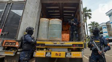 Petugas Direktorat Jenderal Bea dan Cukai (DJBC) Kementerian Keuangan menunjukkan barang bukti pakaian bekas selundupan di Jakarta, Rabu (11/3/2020). DJBC menyita 874 ballpress pakaian bekas yang diangkut delapan truk tronton. (merdeka.com/Imam Buhori)