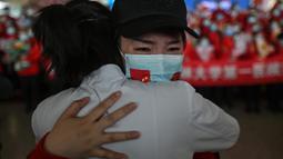 Staf medis dari Provinsi Jilin (kanan) menangis ketika memeluk perawat dari Wuhan setelah bekerja bersama menangani pandemi Covid-19 selama upacara pelepasan di Bandara Tianhe, Wuhan, provinsi Hubei, Rabu (8/4/2020). Pemulangan itu bersamaan dengan dicabutnya lockdown Wuhan. (Hector RETAMAL/AFP)