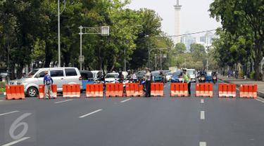 Petugas Satlantas melakukan penutupan Jalan Medan Merdeka menuju Istana Negara, Jakarta, Jumat (30/10). Berbagai antisipasi dilakukan jajaran kepolisian untuk mengamankan jalannya aksi demo ribuan buruh di depan Istana. (Liputan6.com/Yoppy Renato)