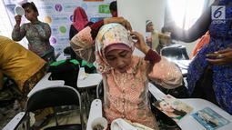 Seorang pengemudi ojek online wanita memasang jilbab jelang peragaan busana di Rawamangun, Jakarta, Jumat (20/4). Kegiatan tahunan ini sebagai bentuk apresiasi GO-Mart DanDan kepada mitra driver. (Liputan6.com/Fery Pradolo)