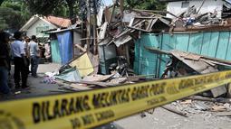 Petugas kepolisian saat memeriksa rumah rusak akibat tertimpa crane di kawasan Kemayoran, Jakarta, Kamis (6/12). Akibat kejidan tersebut menyebabkan tiga orang luka-luka. (Merdeka.com/Iqbal S. Nugroho)
