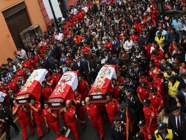 Ribuan warga, beserta petugas dan kerabat mengiringi upacara pemakaman tiga petugas pemadam kebakaran yang tewas di sebuah pabrik sepatu di kota Lima, Peru (21/10). (Reuters/Guadalupe Pardo)