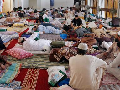 Suasana saat umat muslim itikaf atau berdiam di masjid dan menyembah Allah pada sepuluh hari terakhir Ramadan di Masjid Grand Faisal, Islamabad, Pakistan, Minggu (26/5/2019). Umat muslim terlihat membawa perlengkapan tidur seperti bantal dan selimut untuk menginap di masjid. (AP Photo/Anjum Naveed)