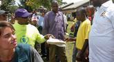 Rapper AS, Kanye West memberikan sepatu kets kepada seorang anak saat mengunjungi Kampung Anak UWESCO di Masulita, Uganda, Selasa (16/10). Kanye West membagikan ratusan pasang Yeezy Boost 350 V2s kepada anak-anak yatim piatu di sana. (AP/Stephen Wandera)