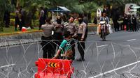 Polisi foto bersama saat menjaga akses jalan menuju Istana Negara, Jakarta, Senin (14/10/2019). Hingga sore hari, polisi masih menutup jalan dikarenakan isu adanya demo mahasiswa yang akan berlangsung hari ini. (Liputan6.com/JohanTallo)