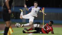 Gelandang Amerika Serikat, Christian Pulisic, terjatuh saat dilanggar pemain Trinidad Tobago pada laga kualifikasi Piala Dunia di Stadion Ato Boldon, Selasa (10/10/2017). Trinidad dan Tobago menang 2-1 atas  Amerika Serikat. (AP/Rebecca Blackwell)