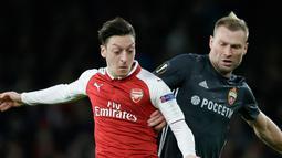 Pemain CSKA Moscow Aleksei Berezutski berebut bola dengan pemain Arsenal Mesut Ozil saat pertandingan Liga Eropa di stadion Emirates, London (5/4). Arsenal menang telak 4-1 atas klub Rusia, CSKA Moskow. (AP Photo / Tim Ireland)