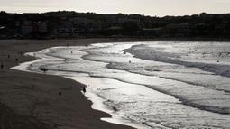 Peselancar menikmati air di Pantai Bondi di Sydney, Selasa, (28/4/2020). Pantai dibuka kembali setelah sempat ditutup selama 6 minggu untuk mencegah penyebaran corona (COVID-19). (AP Photo/Rick Rycroft)