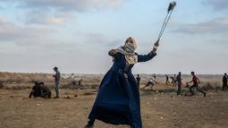 Wanita Palestina memakai ketapel untuk melemparkan batu ke arah pasukan Israel saat bentrok di Khan Yunis, Jalur Gaza, Jumat (13/9/2019). Unjuk rasa ini digelar setiap Jumat untuk menuntut kepulangan ke Tanah Palestina. (SAID KHATIB/AFP)