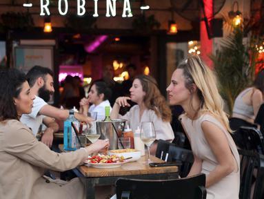 Orang-orang menikmati makanan di kafe di Abima Square di kota Tel Aviv, Israel (20/5/2021). Israel dan dua kelompok bersenjata utama Palestina di Gaza, Hamas dan Jihad Islam, menyetujui gencatan senjata untuk mengakhiri konflik selama 11 hari. (AFP/Gideon Markowicz)