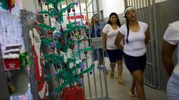 Narapidana wanita meninggalkan sel mereka untuk mengikuti perayaan Natal di Penjara Nelson Hungria, Rio de Janeiro, Brasil, Kamis (13/12). Acara ini dilakukan setiap tahun. (AP Photo/Silvia Izquierdo)