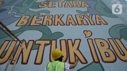 Muralis perempuan menyelesaikan pembuatan mural pada dinding di kawasan Juanda, Jakarta, Rabu (16/6/2021). Ini adalah mural ketiga di Jakarta dengan menggunakan cat Graphenstone. (merdeka.com/Imam Buhori)