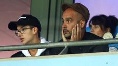 Pelatih Manchester City, Pep Guardiola bereaksi saat melihat timnya melawan Olympique Lyon pada Grup F Liga Champions di tribun penonton Stadion Etihad, Rabu (19/9). Guardiola duduk di bangku penonton karena sedang menjalani sanksi. (AP/Dave Thompson)