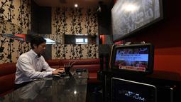 Foto 30 Agustus 2018, pengusaha Hideyuki Aoki bekerja di dalam ruangan karaoke sewaan di Tokyo. Perusahaan karaoke terbesar Jepang, Daiichikosho, menyewakan ruang karaoke untuk tempat kerja para karyawan yang bosan di kantor. (Toshifumi KITAMURA/AFP)