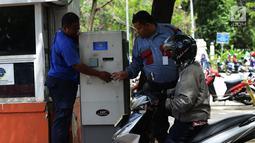 Petugas melayani pengendara motor mengambil karcis parkir di Kawasan Irti Monas, Jakarta, Kamis (3/1). Tarif layanan parkir baru tersebut kemudian akan diterapkan di sejumlah lokasi parkir lainnya. Merdeka.com/Imam Buhori)