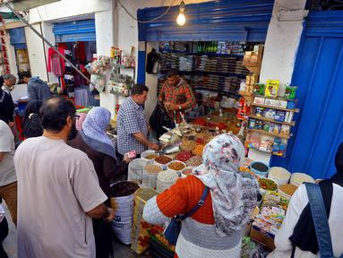 Warga membeli produk makanan untuk persiapan menyambut datangnya bulan Ramadan di Ibu Kota Tripoli, Libya, 1 Mei 2019. Kendati tertekan lantaran dibayang-bayangi oleh pertempuran antara pasukan pemerintah dengan pemberontak, warga Tripoli tetap antusias menyambut Ramadan. (MAHMUD TURKIA/AFP)