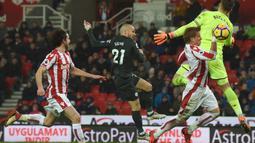Sepakan David Silva (tengah) melewati adangan kiper Stoke City, Jack Butland pada lanjutan Premier League di Bet 365 Stadium, Stoke, (13/3/2018). Manchester City menang 2-0. (AFP/Paul Ellis)