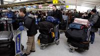 Para penumpang menunggu penerbangan yang tertunda di Terminal 4 Bandara Internasional John F Kennedy (JFK), New York, Senin (8/1). Sebelumnya, bandara mengalami rentetan penundaan akibat suhu ekstrem yang terjadi di wilayah timur laut AS (AP/Richard Drew)