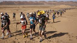Para peserta bersaing dalam kejuaraan Marathon des Sables ke-32 tahap ketiga di Gurun Sahara, selatan Maroko, Selasa (11/4). Para peserta diwajibkan membawa tas berisikan makanan, perlengkapan tidur dan material lainnya. (JEAN-PHILIPPE KSIAZEK/AFP)