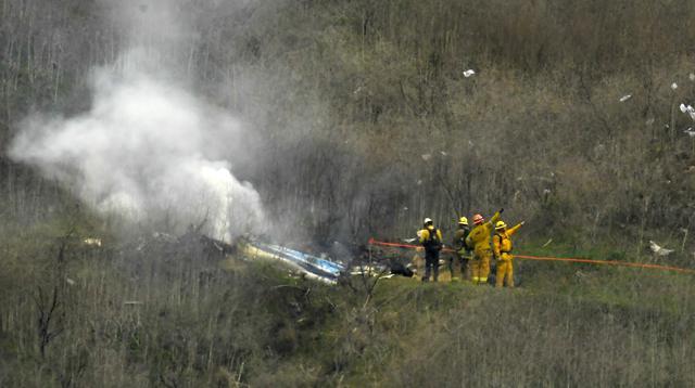Petugas kebakaran sedang memadamkan api yang berada di helikopter yang menyebabkan Kobe Bryand tewas. (AP Photo/Mark J. Terrill)