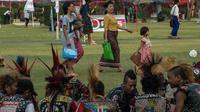 Warga melintas di depan sekelompok anak punk yang berkumpul di sebuah taman di pusat kota Yangon, Myanmar (12/4). Selain Myanmar Empat negara Asia tenggara seperti Thailand, Kamboja dan Laos juga menggelar festival air.  (AFP Photo / Roberto Schmidt)