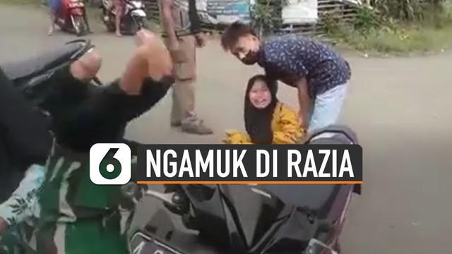 Video seorang pengendara motor perempuan mengamuk di jalan saat di razia petugas polisi karena tidak memakai masker dan helm.