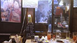 Seorang pemilik bar yakitori menyiapkan makanan di area jalan malam belakang pusat kota Tokyo (4/10/2019). Yakitori terbuat dari potongan daging semua bagian ayam seperti dada, paha , kulit, hati dan jeroan lainnya dan dimasak di atas arang. (AP Photo/Mark Baker)