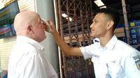 Petugas Daops 3 Cirebon memeriksa suhu tubuh calon penumpang di stasiun sebelum menikmati perjalanan. Foto (Liputan6.com / Panji Prayitno)