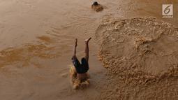 Anak-anak berenang di Sungai Ciliwung yang meluap di kawasan Rawajati, Jakarta, Jumat (26/4). Tingginya volume debit air yang berasal dari Bogor tidak menyurutkan niat anak-anak itu untuk tetap berenang, meskipun berbahaya bagi keselamatan. (Liputan6.com/Immanuel Antonius)