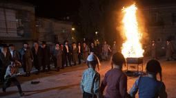 Yahudi Ultra-Ortodoks menari  di samping api unggun selama hari libur Yahudi perayaan Lag Ba'Omer di Bnei Brak, Israel, Kamis (29/4/2021). Liburan Lag Ba'Omer, menandai berakhirnya wabah yang dikatakan telah membinasakan orang Yahudi selama zaman Romawi. (AP Photo/Sebastian Scheiner)