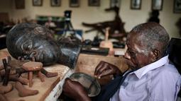 Edward Njenga bekerja memperbaiki patung karyanya yang berjuluk 'Women's Guild Member (2008)' di bengkelnya, Nairobi, Kenya, Senin (12/3).  Njenga lahir pada tahun 1922 dan menjadi pematung terkemuka. (AFP PHOTO/Yasuyoshi CHIBA)
