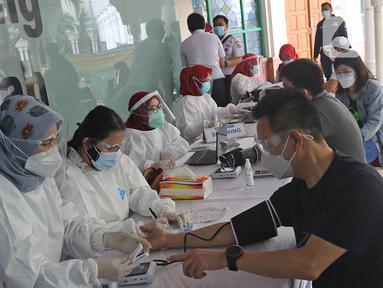Pedagang menjalani penapisan kesehatan saat vaksinasi COVID-19 di Pasar Tanah Abang Blok A, Jakarta, Rabu (17/2/2021). Total sasaran vaksinasi tahap kedua ini mencapai 38.513.446 yang terdiri dari 21 juta lebih lansia, dan hampir 17 juta untuk pekerja pelayanan publik. (Liputan6.com/Herman Zakharia)